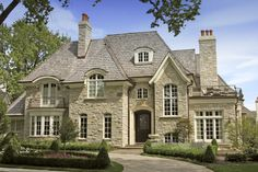 Chimney pots, architectural wood shake roof, casement windows, window stone arches, window millwork, front door, copper gutters and flashing, stone exterior, house scale and proportion, and the landscaping. Everything! Everything is perfect about this house.