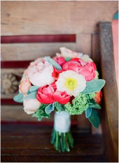 A stunning bridal bouquet with fluffy peonies in vivid shades of pink by Hollyflora.