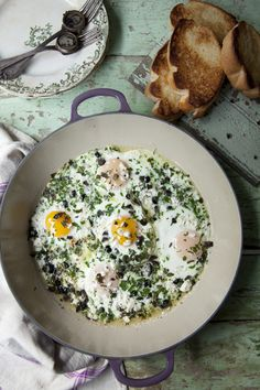 Greek baked eggs with fresh herbs, feta and Kalamata olives.