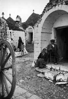 Alfred Eisenstaedt: Row of trulli homes. Trulli are made from limestone boulders and feature conical or domed roofs. Roofs of trulli are painted with signs to ward off evil. Alberobello, Italy, 1947