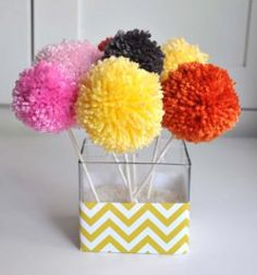 Brighten up any boring tabletop or kids' dresser with a Cheerful Yarn Pom Pom Bouquet! First, learn how to make yarn pom poms with this tutorial; then learn how to turn those playful little pom poms into a brilliant bouquet of color.