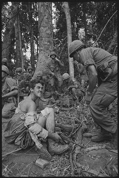 23 Nov 1967, Dak To, South Vietnam. Hill 875 Casualty. Dak To, South Vietnam: Swathed in battle dressings, but still gripping his weapon, a wounded soldier of the 173rd Airborne awaits evacuation from Hill 875. American troops captured the summit of Hill 875, climaxing the longest and costliest battle of the Vietnam war. The battle claimed the lives of 280 Americans and nearly 1400 North Vietnamese. © Bettmann/CORBIS