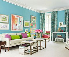 A contemporary turquoise living room with hits of purple & lime, with a large cream sofa and a pair of small square coffee tables