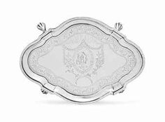 A SILVER TEAPOT STAND -  MARK OF PAUL REVERE, JR., BOSTON, CIRCA 1785 -  Shaped oval, on four paw feet, with molded rim, the field with bright-cut engraved neo-classical decoration, the center later engraved with the monogram BF within a cartouche, marked on reverse (Kane mark B) 6 3/8 in. (16.2 cm.) long; 4 oz. 10 dwt. (150 gr.) silver teapot, circa 1785, neoclass decor, 162 cm, paul rever, teapot stand