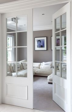 Make a pocket door like this and put photographs over glass panes for now when it's a bedroom then remove later.