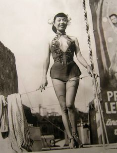 The Carnival Girl This is an old photograph is of a young Asian woman who appears to be getting ready to perform in a carnival show. There is nothing to identify who she was or exactly when or where the photograph was taken.