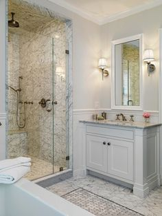 Chic marble bathroom with pale gray walls paint color, marble tiles floor with marble basketweave inset tiles, pale gray single bathroom vanity with marble countertop, chair rail & subway tiles backsplash, single sconces flanking white beveled bathroom mirror, seamless glass shower with marble tiles shower surround and rain shower head.