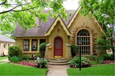 Charming small brick house with burgundy front door and rounded windows