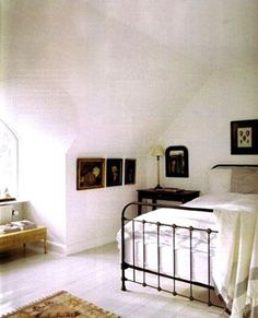 Wrought iron bed + white bedroom. An almost monastery-like feel to this room.