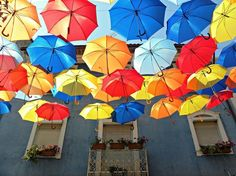 Colorful umbrellas fill the street in Agueda, Portugal for an installation for the Agitagueda Festival. color umbrella, umbrella fill