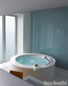 """A Sexy Soaking Tub  Created to be the """"ultimate spa experience,"""" this enviable bathroom by designer Michael Richman offers a breathtaking view of downtown Chicago from the circular tub."""