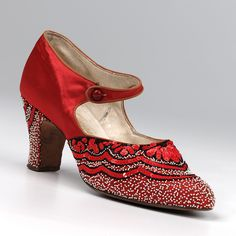Red satin, bead embroidered bar shoe. Pointed toe. 2.6 inch embroidered louis heel. Bar to button over instep. Embroidered with red sequins and black and white beads. White kid lining and sock stamped: for Harrods Ltd. Sole stamped: Made in France. Right foot. Made in about 1925. Image via Northampton Museums & Art Gallery. #vintage #shoes #heels #fashion #1920s