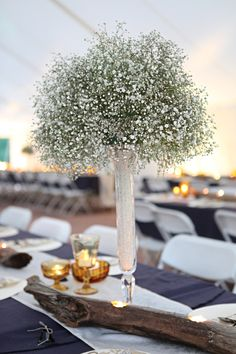 Baby's breath center piece. Glass vase filled with rice, topped off w/ florist foam and baby's breath.