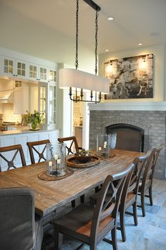 Gorgeous dining room with see through fireplace into living room and pass through to kitchen. Via House of Fifty blog