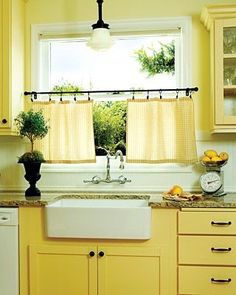 yellow vintage-inspired kitchen with cafe curtains, schoolhouse pendant and farmhouse apron sink.