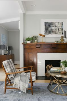 I love the original dark wood with the painted brick fireplace. And I love that the fireplace divides the rooms.  If only it was a working fireplace.