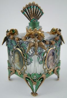 antique perfume bottle with delicate birds facing upwards, ready for flight