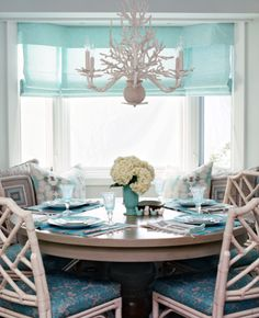 Gorgeous turquoise blue and gray coastal dining room design with turquoise blue silk roman shades on bay windows, white branches chandelier, round gray pedestal dining table, built-in dining bench, white faux bamboo dining chairs with turquoise blue & gray damask cushions, turquoise blue and gray pillows and soft blue walls paint color. white gray turquoise blue dining room colors.