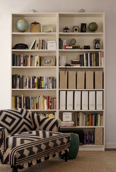 Good shelf organization by mixing being able to see some of the spines of books but some of those magazine folders for a little bit of uniformity without having to use them on the entire bookshelf. I also really like the chair, apparently it's made from old bridal rugs.