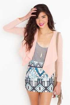 Pink jacket with grey shirt, gold feather necklace and blue patterned skirt.