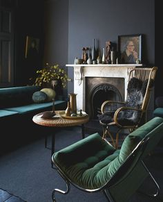 living room, dark walls, charcoal grey, green velvet, retro, tufted, sofa, coffee table, marble fireplace, portrait, art, rocking chair, fur, vase, mantlepiece display, styling repin.