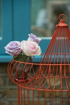 An unadorned birdcage transforms into an outdoor room centerpiece with a coat of cayenne paint and a petite flower arrangement. | Charlotte's Locks No.268 (birdcage), Dix BlueTM No.82 (window frame), @Farrow & Ball