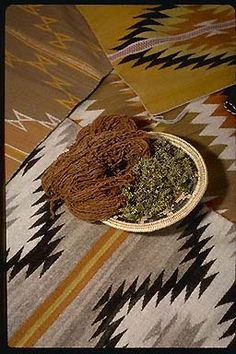 """Before weaving a rug or blanket, members of the Ramah Navajo Weavers Association raise and shear their own sheep, spin the yarns, and dye them with vegetal dyes. The warm browns in this skein of yarn and these weavings come from """"ground lichen"""" (Xanthoparmelia chlorochroa), shown loose in the basket.  Photograph copyright Stephen/Sylvia Sharnoff"""