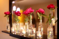 multiple small glass jars with one flower