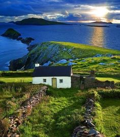cottage and stone fences where land meets ocean and sky in Ireland