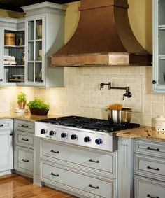 A swath of copper warms up stainless appliances. Paired with distressed painted cabinets, this sculptural, bell-shaped hood adds even more old-world charm.   Photo: Courtesy of Dacor   thisoldhouse.com