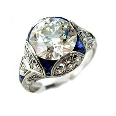 A diamond, sapphire and platinum ring centering a European-cut diamond, accented by calibré-cut sapphire and smaller European-cut diamonds, on a pierced and engraved mount. Art Deco or Art Deco style.