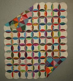Great quilt...four patches on one side to faux cathedral window. Sew white to four patch in circle shape. Cut slit in white side where it will be hidden when turned and folded over. Turn RSO then sew circles together.