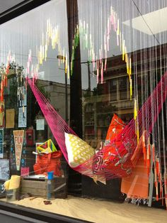 i'm looking at this window display for summer made with popsicle sticks dipped in paint and strung on different sized lengths of fishing line to create shapes and thinking about the possibilities for decorating windows for christmas