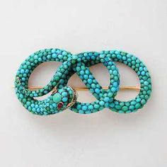 A Georgian turquoise snake brooch, pave-set with cabochon-cut turquoises, the eyes set with oval shaped faceted rubies, set in silver, c. 1840