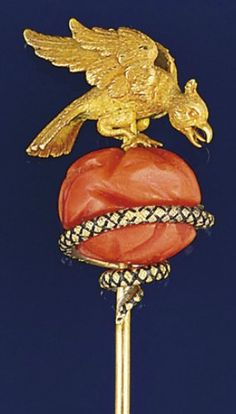 An Early Victorian gold coral, diamond and enamel stickpin  Modelled as a chased gold eagle alighting on a coral, corallium, boulder with gold and black enamel coiled serpent with rose-cut diamond single stone head, circa 1840