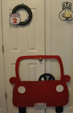 "Transportation / car and truck themed 2nd birthday party decorations - wreath wrapped in black ribbon with puffy paint road lines, route 2 sign from google images, and a matchbox car hot glued on  -red car photo booth-cardboard cutout covered with red duct tape with license plate designed in Microsoft Word and ""laminated"" with packing tape"