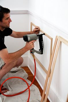 EASY paneled wainscoting solid wood moldings used, assembled and secured in place with a finish nail gun instead of glue.