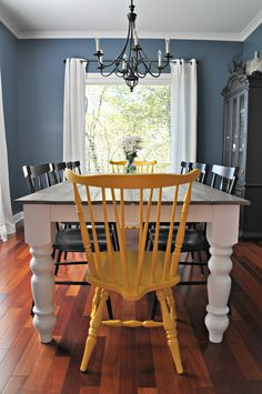 Great dining room decor.  Love the wall color and yellow chairs!