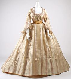 Satin-striped silk, French, ca 1865. Square neck bodice, functional buttons; open sleeves; pleated eliptical skirt, flat front panel. Shown with coordinating belt. MET