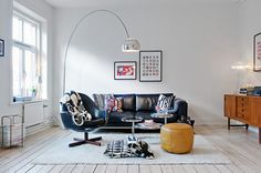 Black leather sofa + colored & textured pillows. Cool lamp