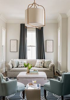 Living room with neutral cream couch, teal side chairs, cocktail ottoman, gold metal and cream shade chandlier