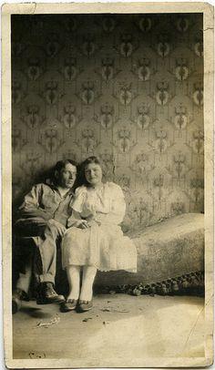 Vintage photo, couple sitting on sagging bed?, old wallpaper