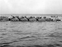 Seabees use Rhino Ferries to shuttle equipment across the English Channel for the assault on D-Day. Here medium tanks for the 111th Naval Construction Battalion are loaded on a Rhino ferry headed for Utah Beach.