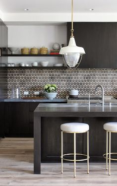 greige design with interesting tile backsplash, cool stools, and retro light fixture