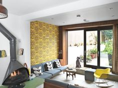 Orla Kiely's London home is color conscious down to the smallest details. For herMalm fireplace, she chose aneutral charcoal finish tobalance the greenlinoleum floor and the Rhododendron wallpaper in Sunflower.