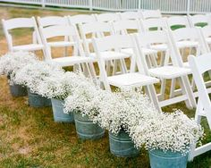 Who knew that tin buckets brimming with baby's breath could have such a big impact when paired with simple white chairs? Such an inexpensive but tasteful way to introduce florals to an aisle.  Source