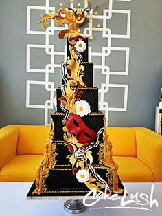Tanvi's Sweet Sixteen. Masquerade cake with gilded leaves, fleur de lis, fabric flowers, buttons and gumpaste ribbon.