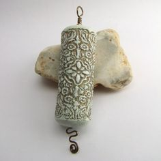 Faux Ivory by Fulgorine - white and gold cylinder bead pendant. This pendant is made from a handmade cylinder bead on a wire axis. The bead is polymer clay with metal leaf embedded into the valleys of the texured surface pattern.