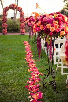 Outdoor wedding idea: Rose petal lined aisle with matching arch and end-row bouquets.