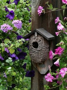 Birdhouse surrounded by garden flowers...lovely.